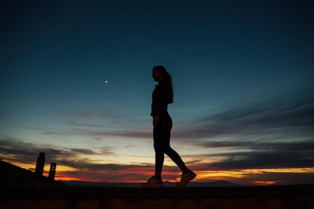Силуэт женщины в деревне на закате.