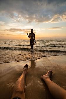 남자 다리와 해질녘 해변에서 여자 실루엣.