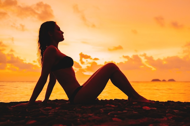 Woman silhouette sitting against sunset on the beach