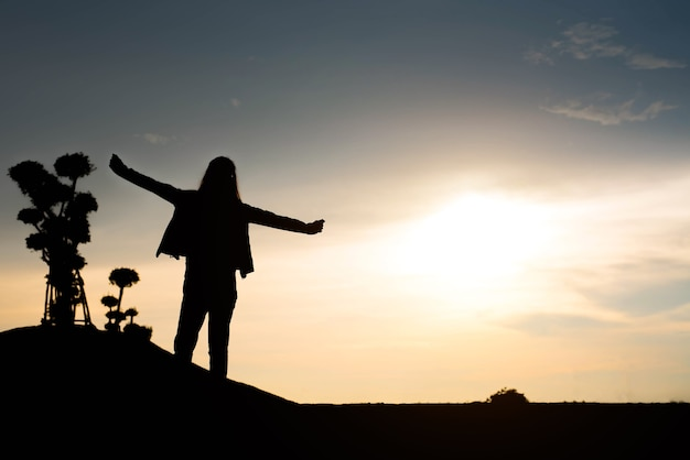 Woman silhouette standing raise hand on sunset