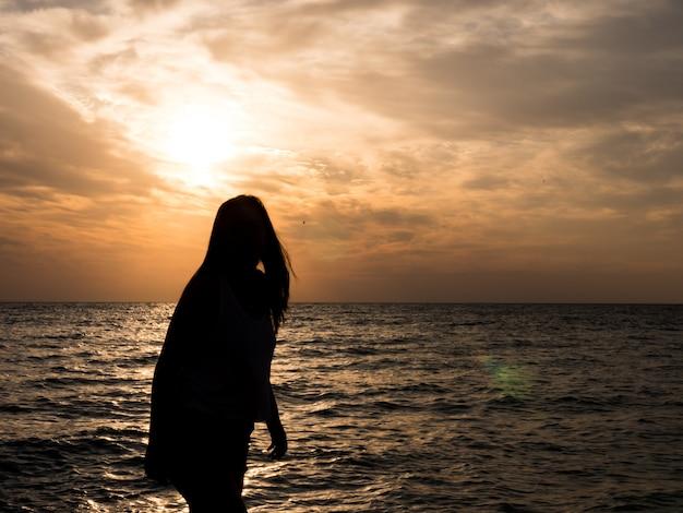 日没時のビーチで太陽を見ている女性のシルエット..ビーチでの休日の観光の女の子