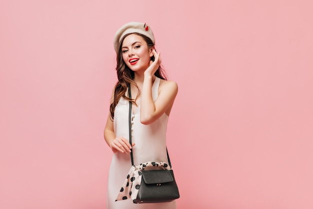 Woman in silk dress and white beret poses with crossbody bag on pink background.