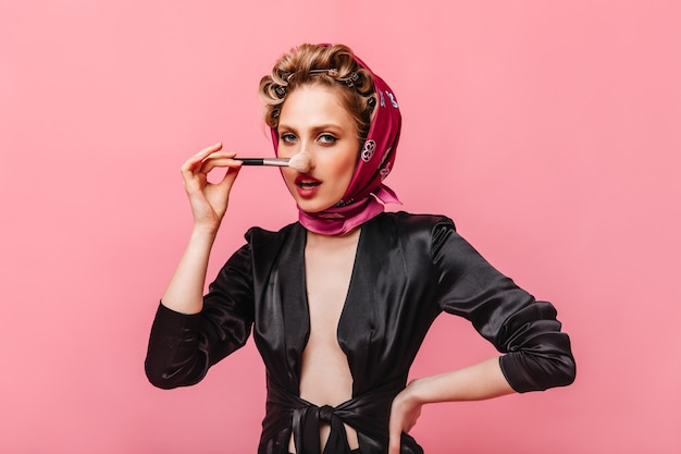 Woman in silk dressing gown and pink scarf holding makeup brush and looking at front