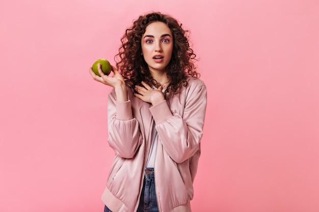 Donna in giacca di seta che tiene mela verde su sfondo rosa