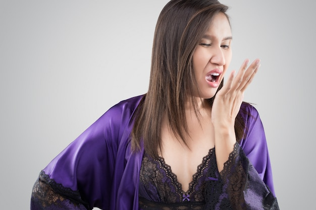 The woman in silk nightgown and purple robe checking her breath with hand