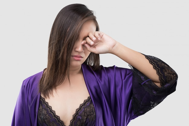The woman in silk purple nightgown and lace robe rubs her eye with