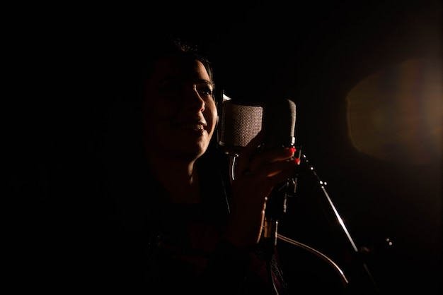 Woman singer singing a song in the recording studio.