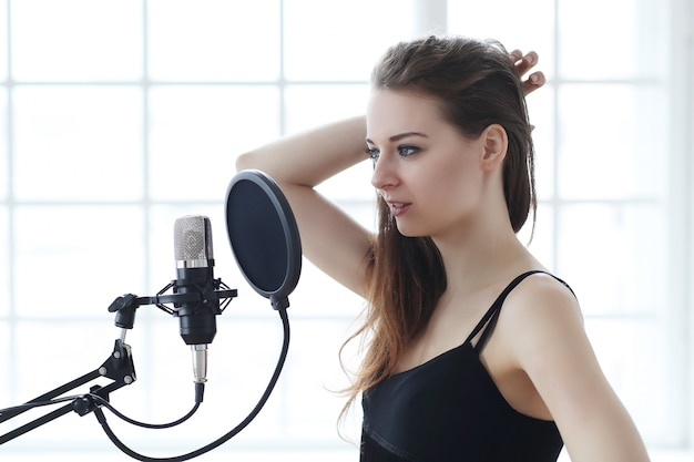 Woman singer with microphone, music studio