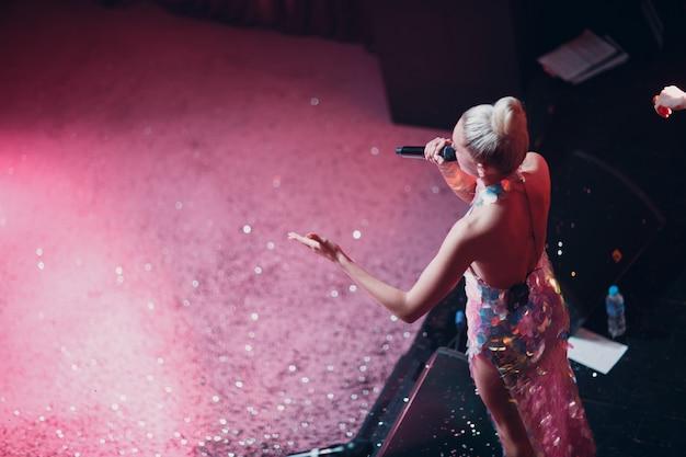 ステージにマイクを持ち、前景に輝きを放つ女性歌手