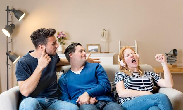 Woman singing loud next to friends while wearing headphones