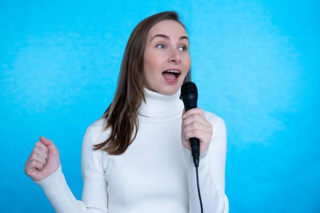 青い壁にマイクで歌う女性。