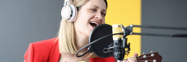 Woman sings and plays guitar with headphones in front of microphone hobby and passion for music