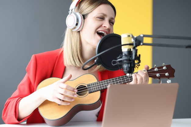 Woman sings and plays guitar with headphones in front of microphone