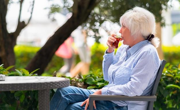 屋外パティオで熱いお茶をすすりながら飲む女性