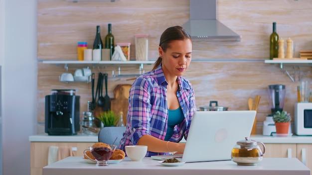 居心地の良いキッチンで朝食時に緑茶をすすりながらラップトップコンピューターで入力する女性。インターネット技術を備えたデバイスを使用して自宅で作業し、朝にガジェットを閲覧、検索します。