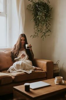 Wfh中に仕事帰りをリラックスするためにお茶をすすりながら女性
