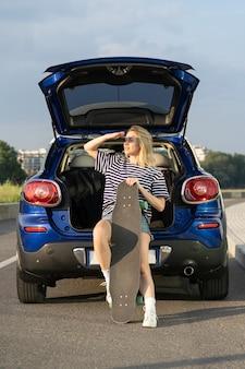 車の後ろに座っている女性は、車で夏休みの冒険ロードトリップ旅行中に日没をお楽しみください