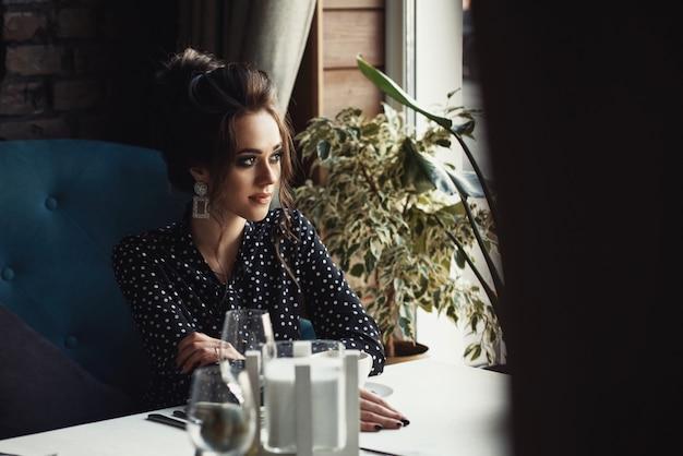 カフェやレストランのテーブルに座っている女性は、ウィンドウを見て、コーヒーを飲む