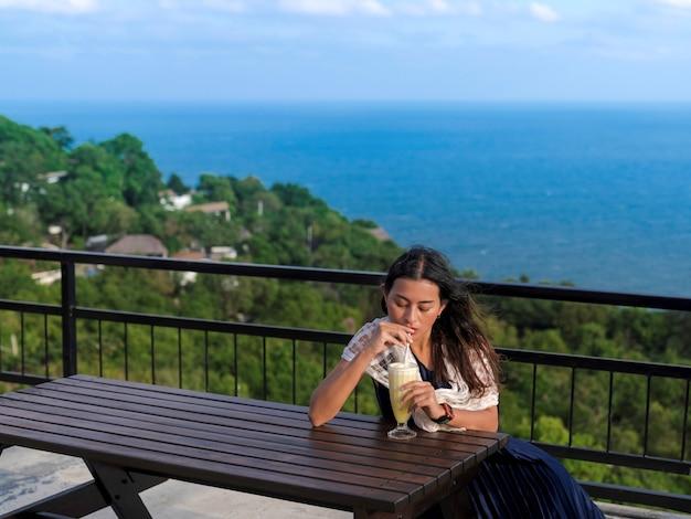 女性は、タイ、スラタニ、タオ島の山頂の海の景色を望むテラスでパイナップルフラッペを飲みながら木製のテーブルに座っています