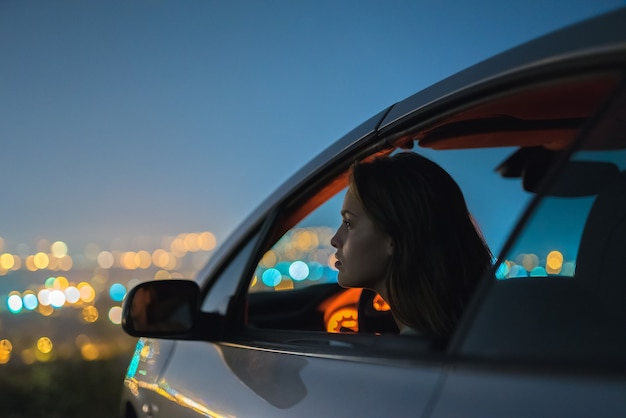 The woman sit in a car on the city lights background. evening night time
