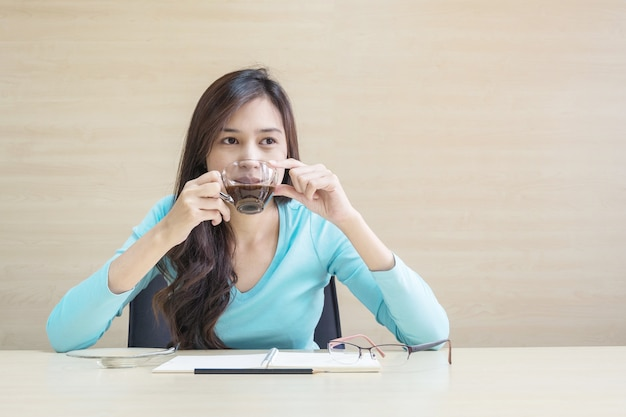 Woman sit for drinking coffee in transparent cup of coffee with thinking emotion