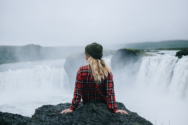 Woman sit on edge of cliff on waterfall