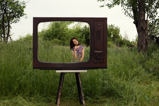 Woman sit in garden grass inside vintage old television frame, modern technology and mental health