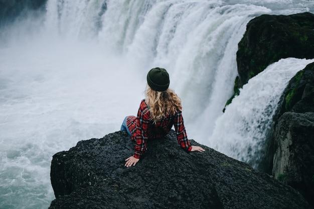 女性は滝の崖の端に座っています
