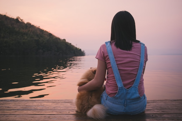 Woman sit and relax with her dog admire the sunset sky and the lake.