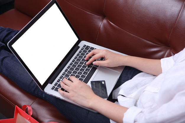 Woman sit on sofa and using mockup laptop with credit card