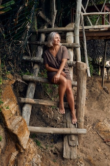 Woman sit on tropical beach house wooden ladder