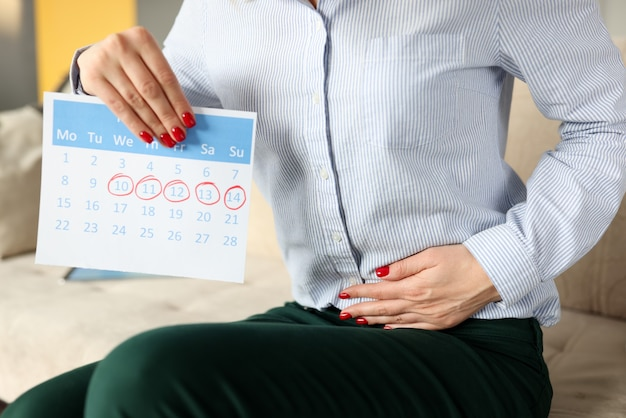 Woman siting on couch and holding on to her sore stomach closeup. menstrual cycle concept