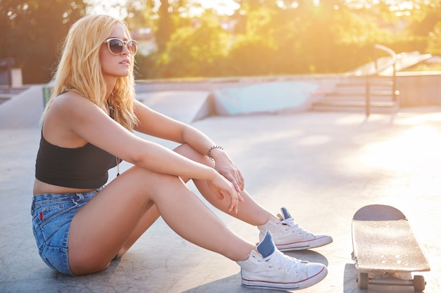 Skatepark에서 지상에 siting 여자