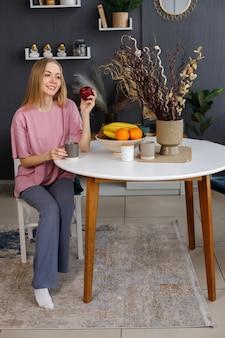 여자는 집에서 사과와 함께 테이블에 앉아