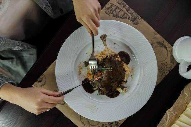 여자는 카페의 나무 테이블에 앉아 와인 소스에 죽으로 구운 오리를 먹고 있습니다. 뜨거운 맛있는 점심. 생활 양식
