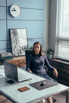 여자는 책상에 앉아서 노트북 화면을 봅니다.