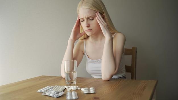 여자는 두통으로 테이블에 앉아있다. 그녀는 앉아서 관자놀이를 만집니다.