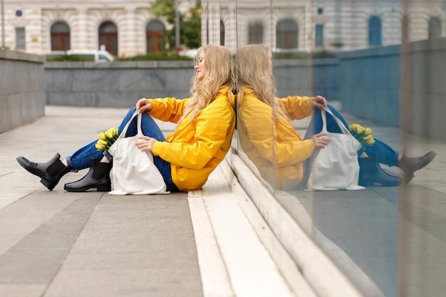 女性は黄色いレインコートで窓に座っています