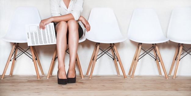 A woman sits in a chair with a resume in hands in anticipation of an interview.