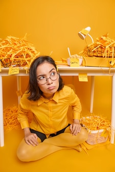 Woman sits crossed legs on floor looks aside poses near workplace develops new design project on yellow