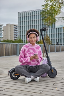 Woman sits crossed legs listens favorite music in earphones wears casual jumper trousers and sneakers rides electric kick scooter poses at urban setting
