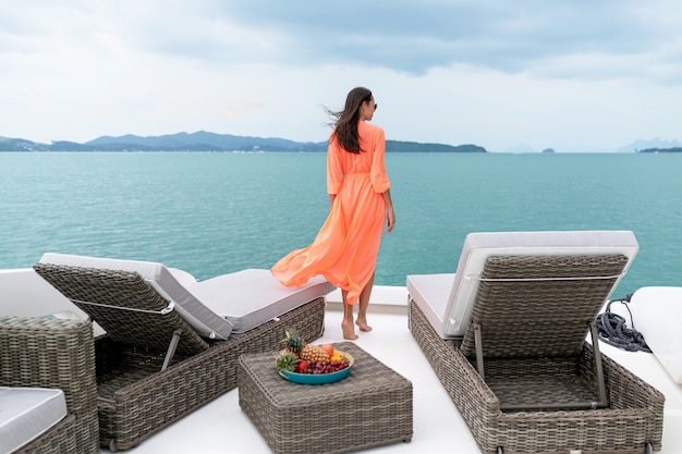 Woman sits on the deck of a yacht