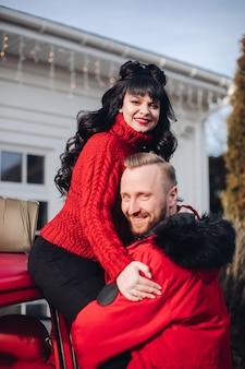 Una donna si siede tra le braccia del marito e sorride vicino a casa