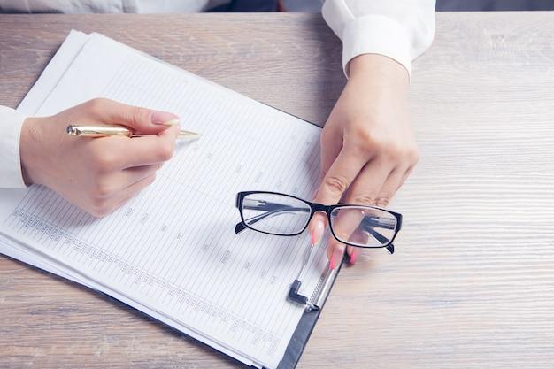 여자는 테이블 앞에 앉아 문서를 검사합니다. 광학 안경