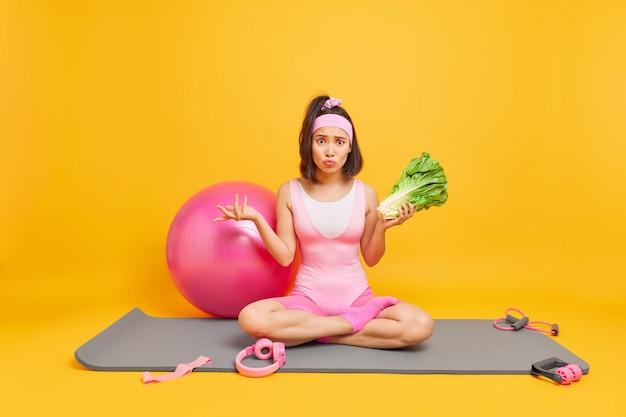 Женщина сидит в позе лотоса на фитнес-коврике, держит зеленый салат в окружении спортивного инвентаря, соблюдает здоровую диету, регулярно делает зарядку, остается дома во время карантина