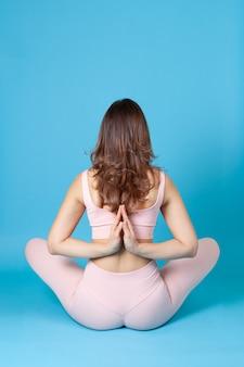 Женщина сидит в позе намасте мудры, заложив руки за спину