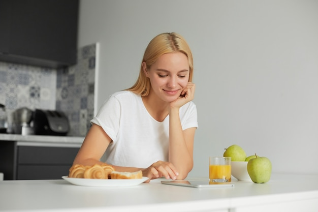 Woman sits at the kitchen table in the morning, smiling, looks at tablet black screen, reading message