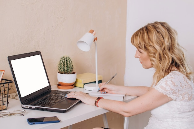 A woman sits at a laptop with a phone and writes in a notebook