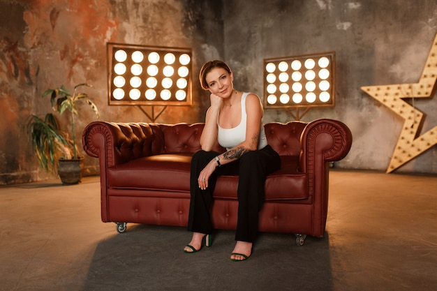 Woman sits on a leather sofa in an expressive pose, looks at the camera.