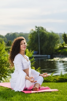 Woman sits in lotus position.